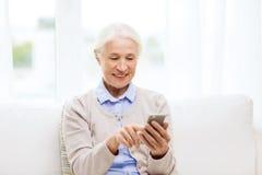 Femme supérieure avec le smartphone textotant à la maison Image libre de droits