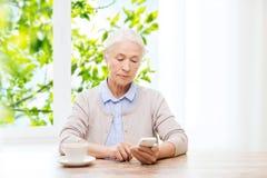 Femme supérieure avec le smartphone textotant à la maison Photo libre de droits