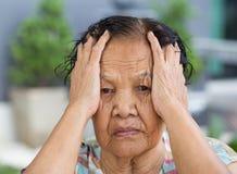 Femme supérieure avec le visage soumis à une contrainte inquiété Images stock