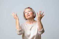 Femme supérieure avec ses mains jusqu'au ciel photos stock
