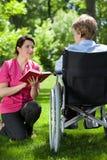 Femme supérieure avec son livre de lecture de travailleur social Photos stock