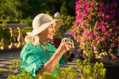 Femme supérieure avec un appareil-photo Images stock