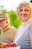 Femme supérieure avec vieux mangeur d'hommes dans un jardin Image libre de droits
