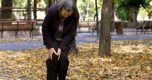 Femme supérieure ayant la douleur de genou marchant dans le parc banque de vidéos