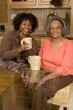 Femme supérieure ayant le café avec sa fille Photographie stock