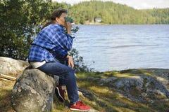 Femme supérieure ayant une boisson chaude par un bord de lac Photo libre de droits