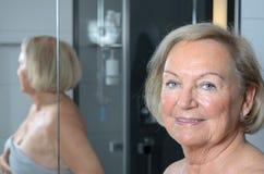 Femme supérieure blonde attirante dans une salle de bains Images stock