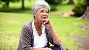 Femme supérieure bouleversée s'asseyant dans la pensée de parc banque de vidéos