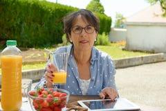 Femme supérieure buvant du jus d'orange dans son jardin Images stock