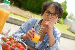 Femme supérieure buvant du jus d'orange dans son jardin Photographie stock