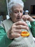 Femme supérieure buvant un verre de thé Image stock