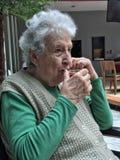 Femme supérieure buvant un verre de thé Photos stock