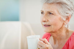 Femme supérieure buvant une tasse de café Photo stock