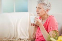 Femme supérieure buvant une tasse de café Photographie stock
