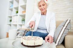 Femme supérieure célébrant seul l'anniversaire photo stock