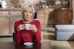 Femme supérieure calme s'asseyant avec une tasse de thé Images libres de droits
