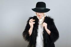 Femme supérieure calme tenant la cigarette Image stock