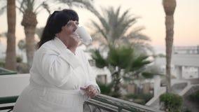 Femme supérieure caucasienne dans le café potable de matin sur la terrasse d'hôtel dans une robe longue blanche de Terry à une st clips vidéos