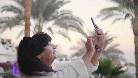 Femme supérieure caucasienne heureuse faisant le selfie sur le smartphone Il devrait être sur la terrasse de l'hôtel dans une rob banque de vidéos