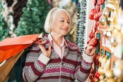Femme supérieure choisissant des ornements de Noël Photos libres de droits
