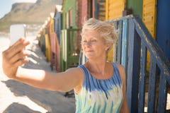 Femme supérieure cliquant sur le selfie tout en se tenant contre la hutte de plage Images stock