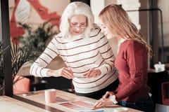 Femme supérieure concentrée prenant des photos de différentes palettes de couleurs Photographie stock libre de droits