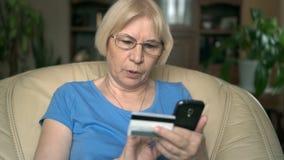 Femme supérieure concentrée s'asseyant dans la chaise à la maison Achat en ligne avec la carte de crédit sur le smartphone clips vidéos