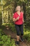Femme supérieure courant à la forêt photos stock