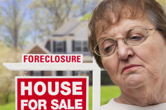 Femme supérieure déprimée devant le signe de Real Estate de forclusion Images libres de droits