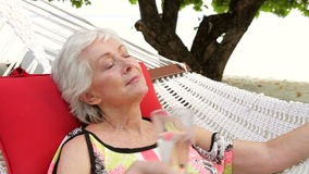 Femme supérieure détendant dans l'hamac de plage avec Champagne banque de vidéos