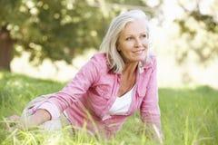 Femme supérieure détendant en Sunny Summer Field Photographie stock