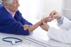 Femme supérieure d'auscultation pour la douleur de poignet image libre de droits