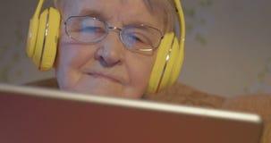 Femme supérieure dans des écouteurs utilisant la tablette clips vidéos