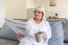 Femme supérieure dans des lunettes lisant un journal Photo libre de droits