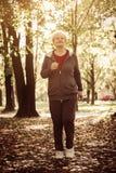 Femme supérieure dans l'exercice d'habillement de sport dans le pré Image stock