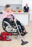 Femme supérieure dans la maison de nettoyage de fauteuil roulant Image libre de droits