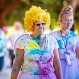 Femme supérieure dans la perruque jaune dans la course d'amusement de frénésie de couleur photographie stock libre de droits