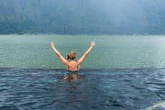 Femme supérieure dans la piscine de nature avec le fond étonnant de montagne Île tropicale Bali, Indonésie Photographie stock