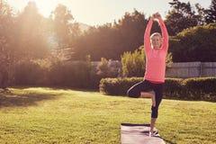 Femme supérieure dans la pose de équilibrage de yoga avec le sunflare de matin Photos stock