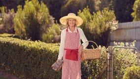 Femme supérieure dans la vitesse de jardinage à sa porte d'arrière-cour Images stock