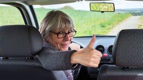 Femme supérieure dans la voiture avec des pouces  Image stock