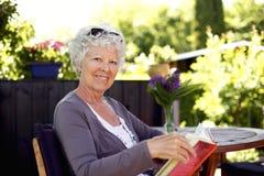 Femme supérieure dans le jardin avec un livre Photographie stock