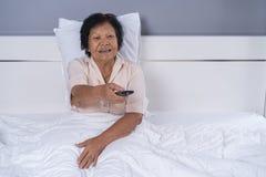 Femme supérieure dans le lit avec la TV à télécommande et observante Photographie stock libre de droits
