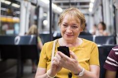 Femme supérieure dans le téléphone de souterrain Image stock