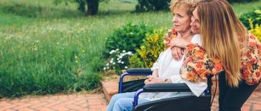 Femme supérieure dans un fauteuil roulant avec sa fille Photo stock