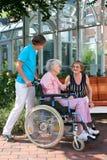 Femme supérieure dans un fauteuil roulant avec son soignant Photos libres de droits
