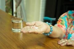 Femme supérieure de concept de soins de santé avec des pilules dans sa main et glas Photographie stock