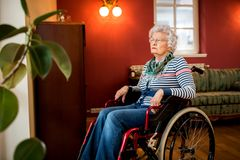 Femme supérieure de solitude s'asseyant dans le fauteuil roulant à la maison de repos Photo libre de droits