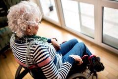 Femme supérieure de solitude triste de dépression dans le fauteuil roulant Photographie stock