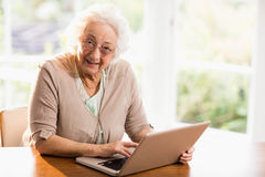 Femme supérieure de sourire à l'aide de l'ordinateur portable Photos libres de droits